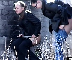 Two girls relieve themselves behind a building